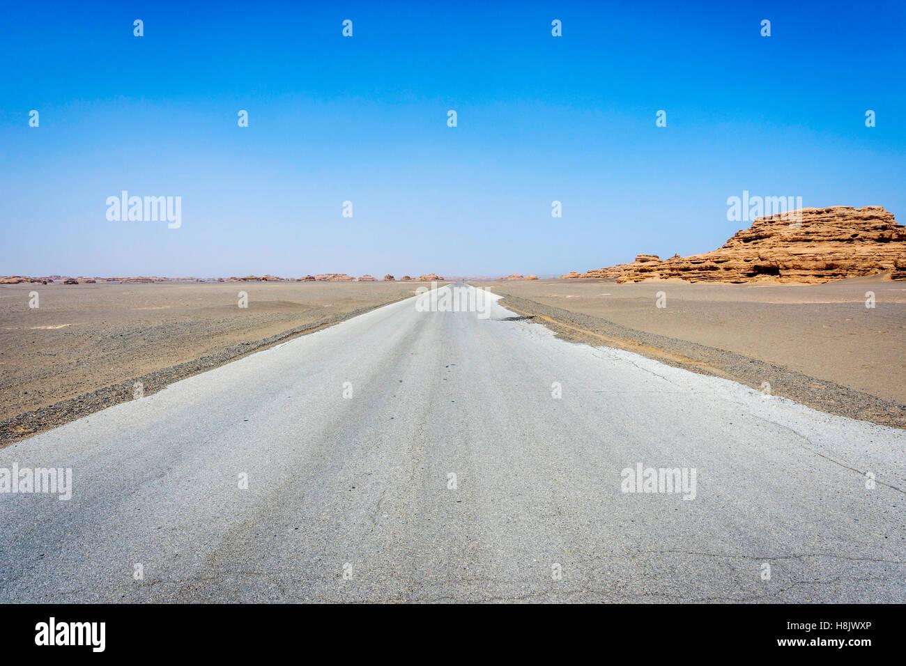 Road straight ahead to Dunhuang Yardang National Geopark, Gobi desert, China - Stock Image