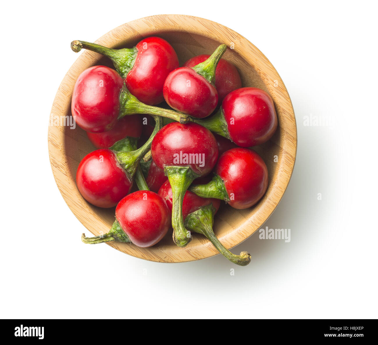 Round red chili peppers in bowl isolated on white background. - Stock Image