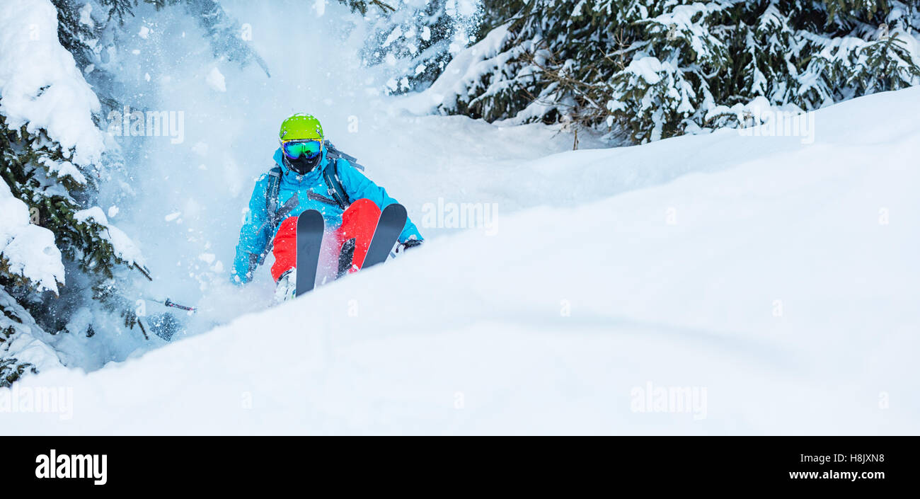 Freeze motion of freerider in deep powder snow, skiing in forest - Stock Image