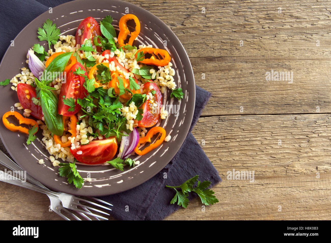 Fresh organic tomato and couscous salad with vegetables and greens - healthy vegetarian salad over rustic wooden - Stock Image