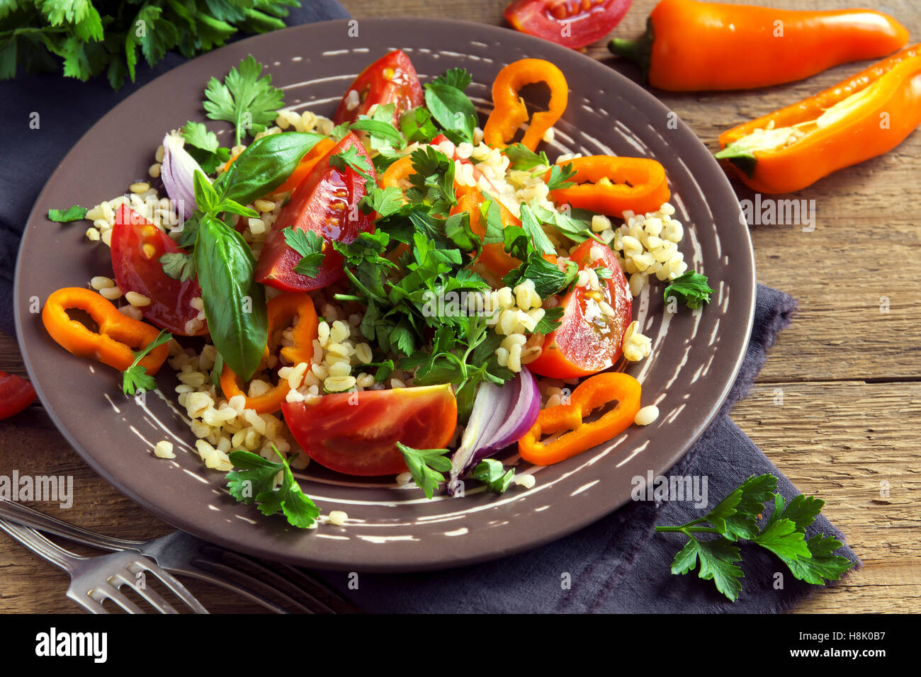 Fresh organic tomato and couscous salad with vegetables and greens - healthy vegetarian salad on rustic plate close - Stock Image