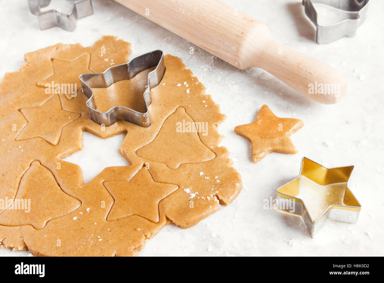 Preparing Christmas gingerbread tree cookies with cutter, dough and rolling pin - homemade festive Christmas bakery - Stock Image