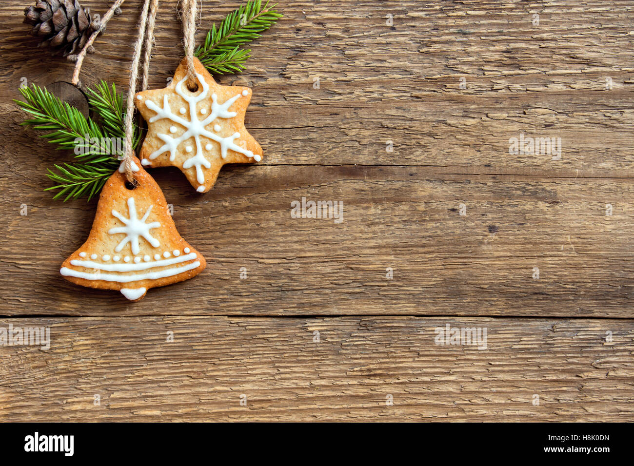 Gingerbread Christmas cookies and fir branches hanging over wooden background with copy space - festive Christmas - Stock Image