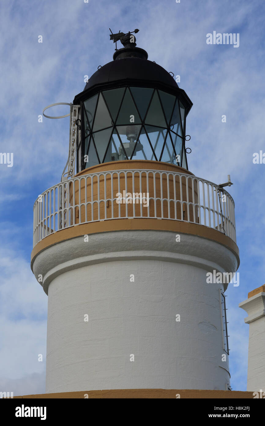The tower of Chanonry Point lighthouse against a blue sky with white clouds - Stock Image