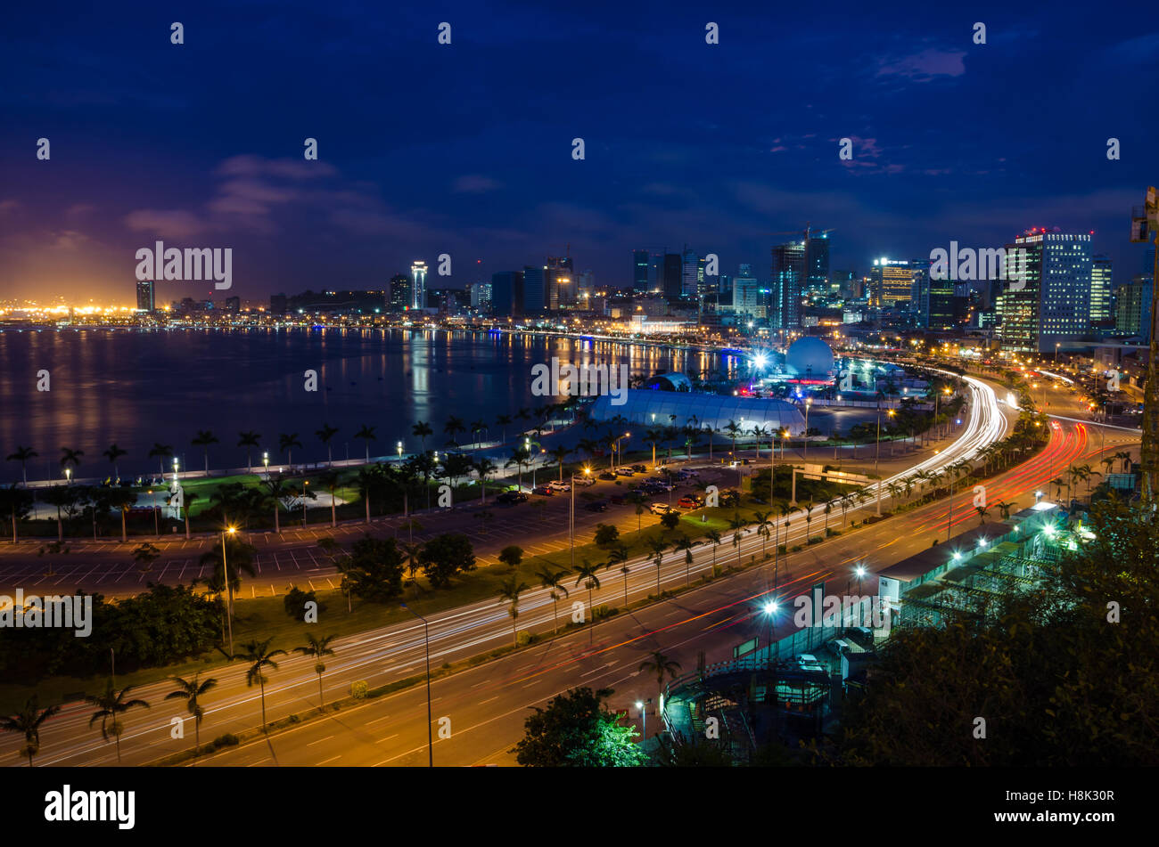 Skyline of Luanda and its seaside during the blue hour. Many lights and high rise buildings. - Stock Image