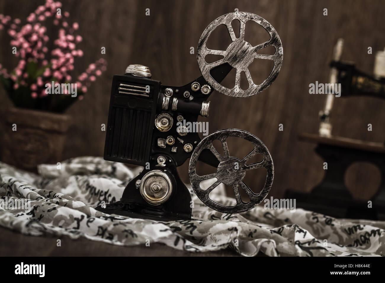 Small nostalgic decorative film camera on brown wooden background - Stock Image