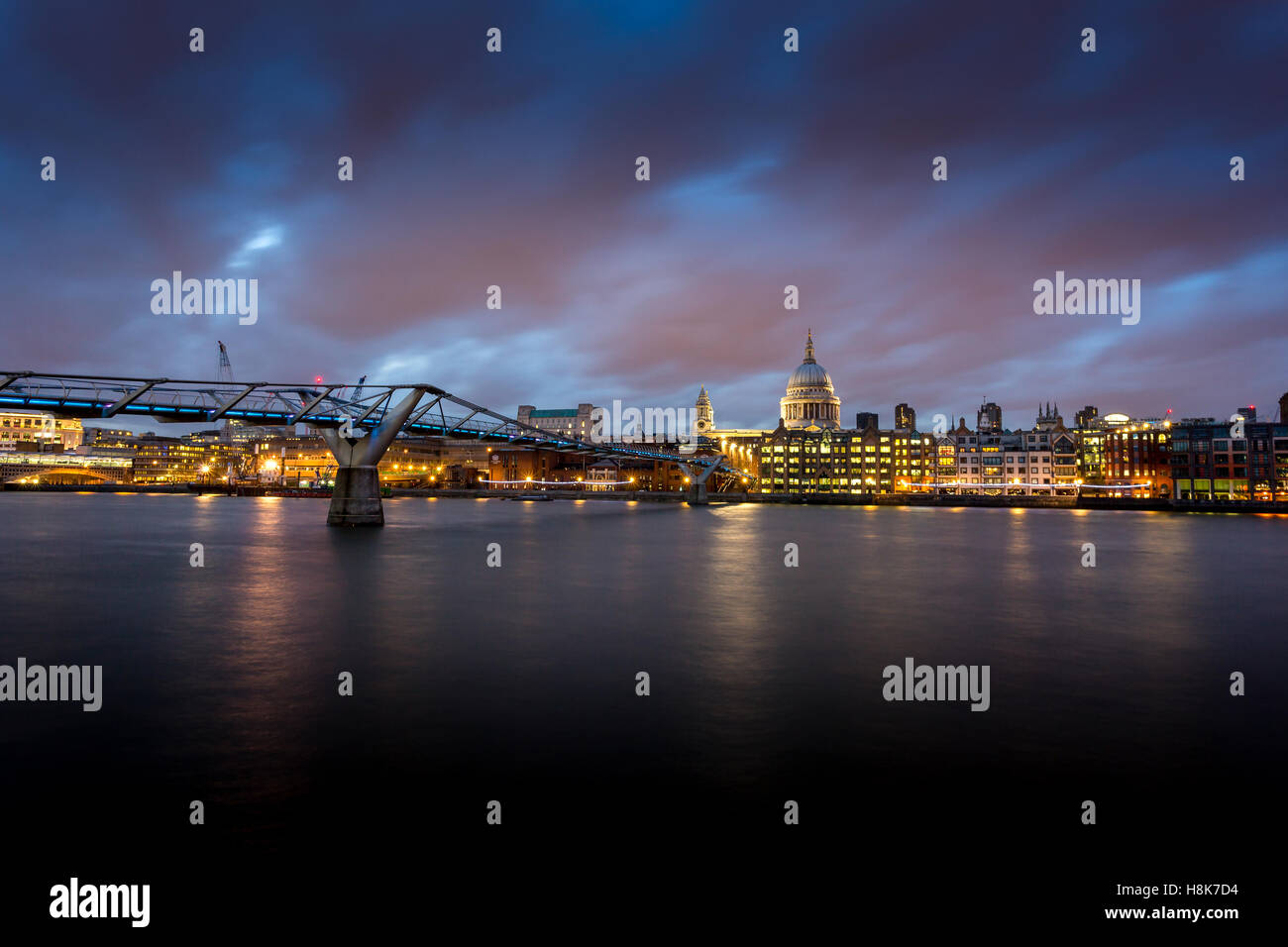 Millennium footbridge London with St Paul's Cathedral at dusk - Stock Image