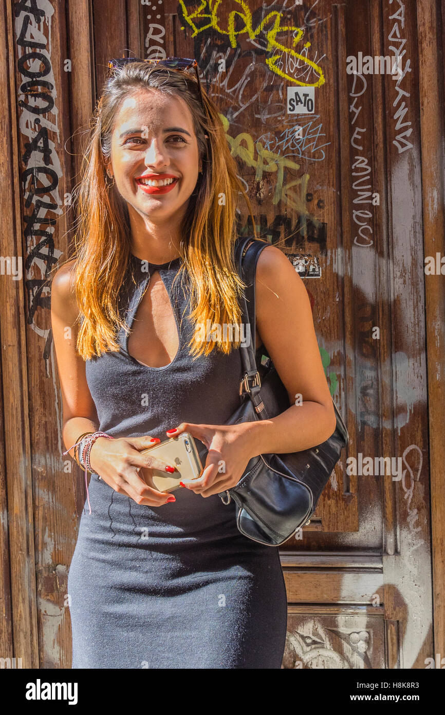 20s something Spanish female smiling as she stands in front of a graffiti covered door in Barcelona. - Stock Image
