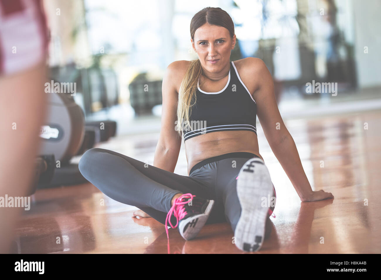 Attractive female sitting on the street and resting after workout - Stock Image