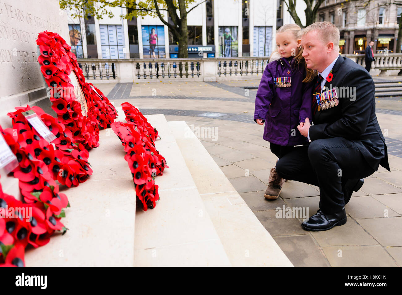 Belfast, Northern, Ireland. 13th Nov, 2016. A soldier wearing medals and his daughter look at the poppy wreaths. - Stock Image