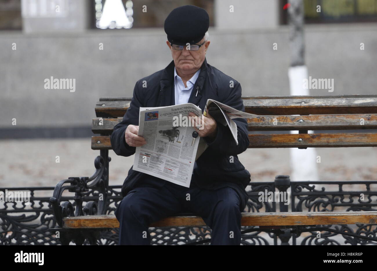 GROZNY, RUSSIA - NOVEMBER 13, 2016: An elderly man sits on a bench reading a newspaper. Valery Matytsin/TASS - Stock Image