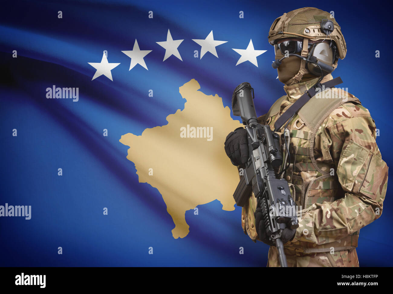 Soldier in helmet holding machine gun with national flag on background - Kosovo Stock Photo
