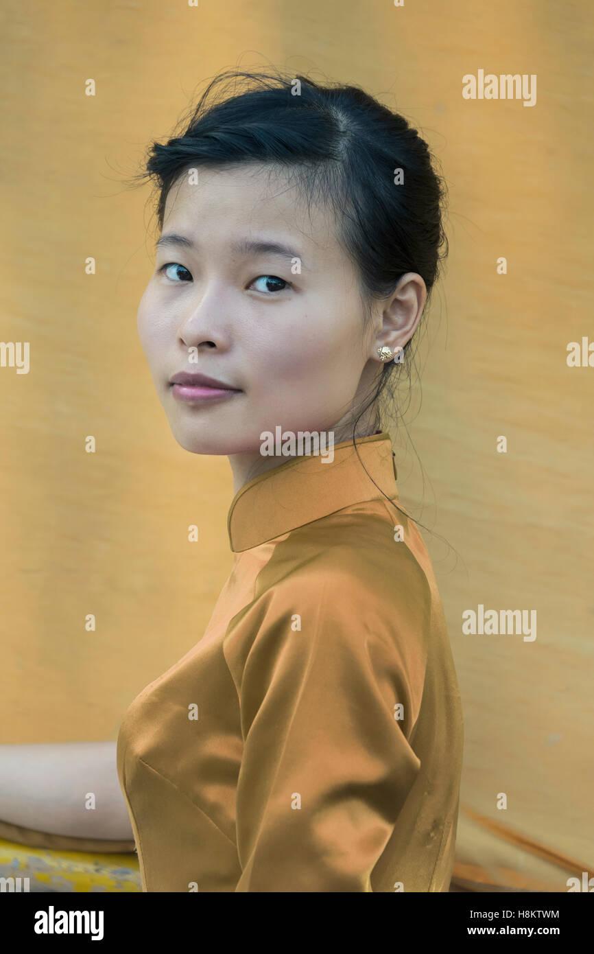 Portrait of a Vietnamese woman against a boat sail, Ha Long Bay, north Vietnam - Stock Image