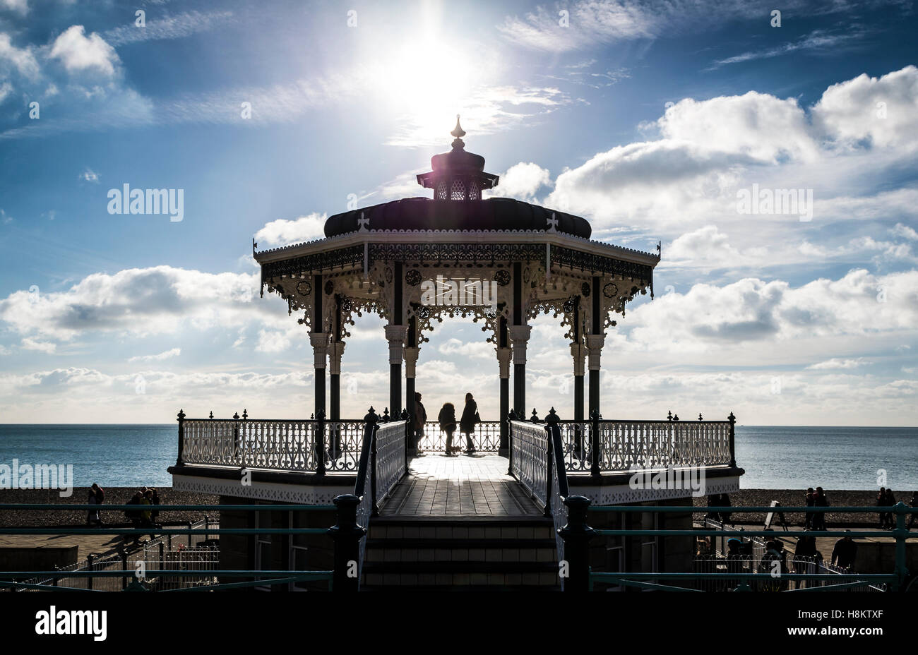 People silhouetted on The Bandstand, Hove, on the seafront. The bandstand is a fine example of Victorian architecture. - Stock Image