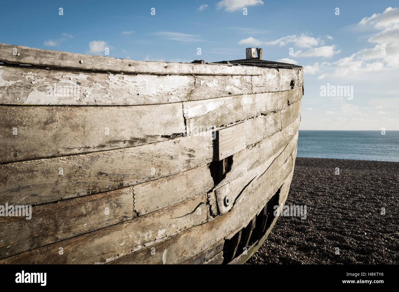 Hull of an old decaying wooden rowing fishing boat with holes in on a pebble beach at the seaside - Stock Image