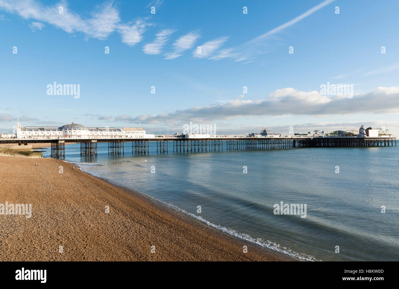 View of Brighton Pier (was Palace Pier) on Brighton Beach on a calm sunny day, Sussex, UK - Stock Image