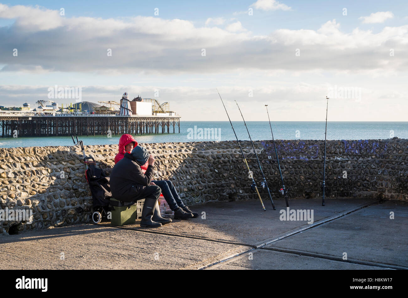 Fishermen with rods leaning up against the groyne wall at Brighton beach with the Palace Pier in the background. - Stock Image