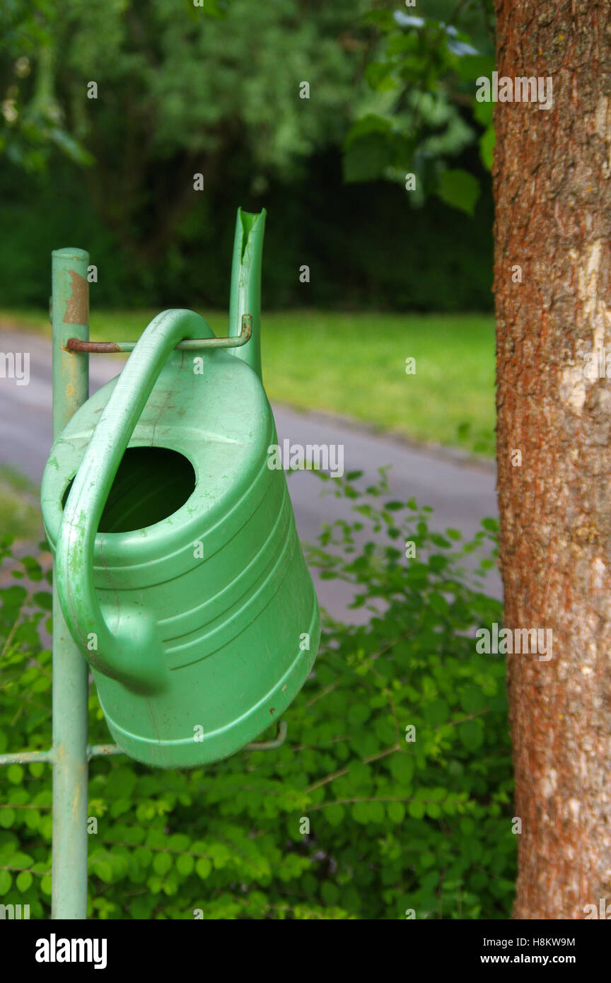 watering can hanging on faucet, gardening, summer. - Stock Image