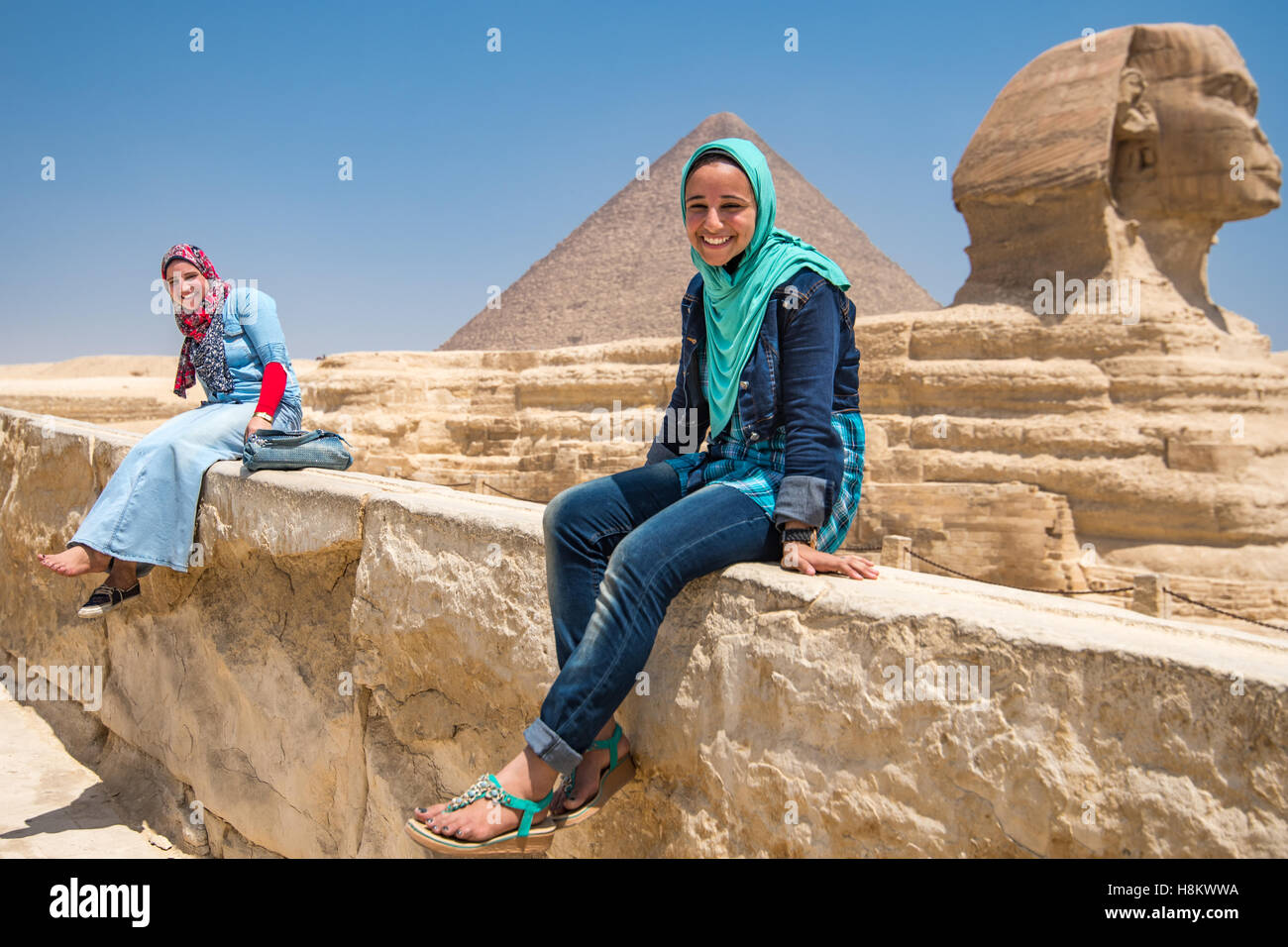 Cairo, Egypt two Egyptian women sit in front of the Great Sphinx of Giza with the Great Pyramids of Giza in the - Stock Image
