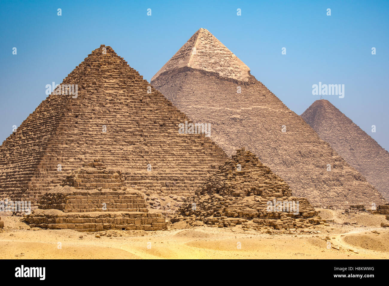 Cairo, Egypt The three Great pyramids of Giza against a clear blue sky. From left to right stands the Pyramid of - Stock Image