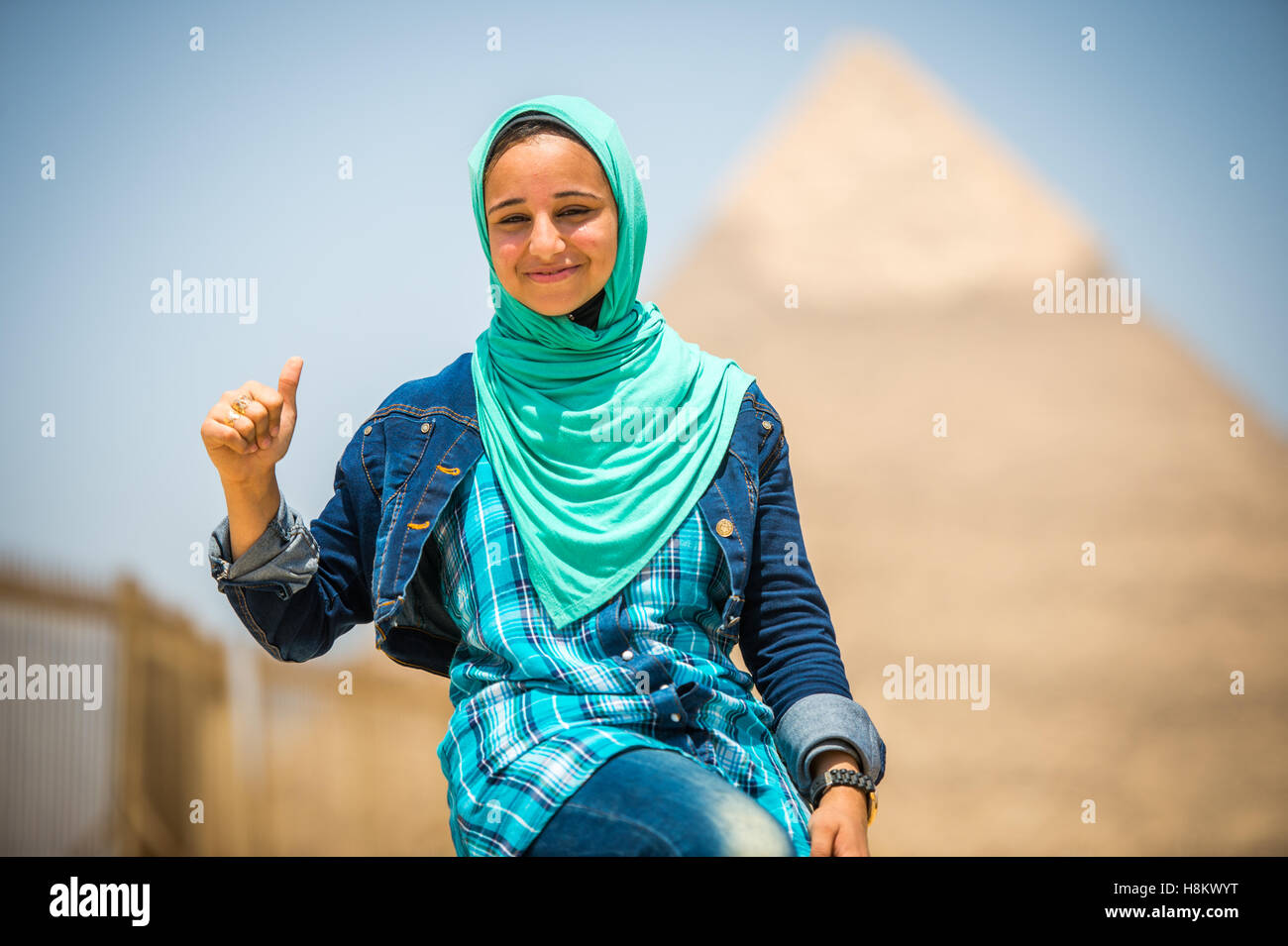 Cairo, Egypt Egyptian woman sitting in front of the Great Pyramids of Giza that are in the background. This particular - Stock Image