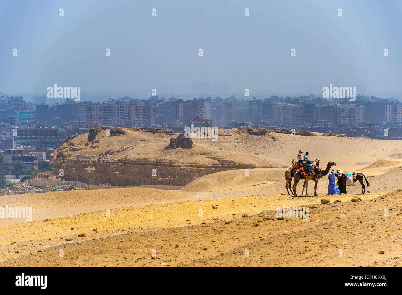 Cairo, Egypt Camel drivers and tourists riding camels and horses through the desert with the city of Cairo in the - Stock Image