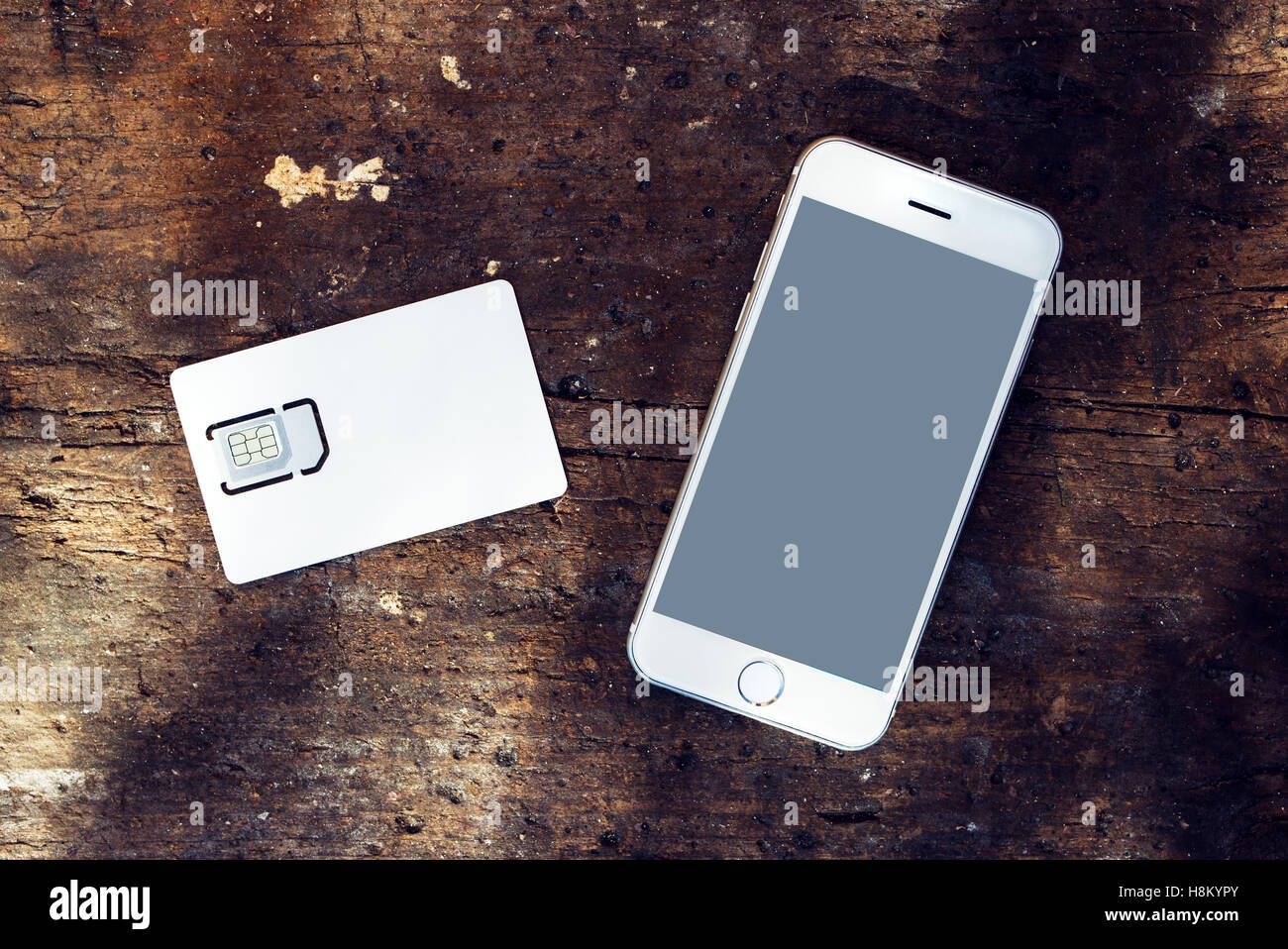Smartphone with blank screen and mobile phone gsm SIM card on the table, top view - Stock Image