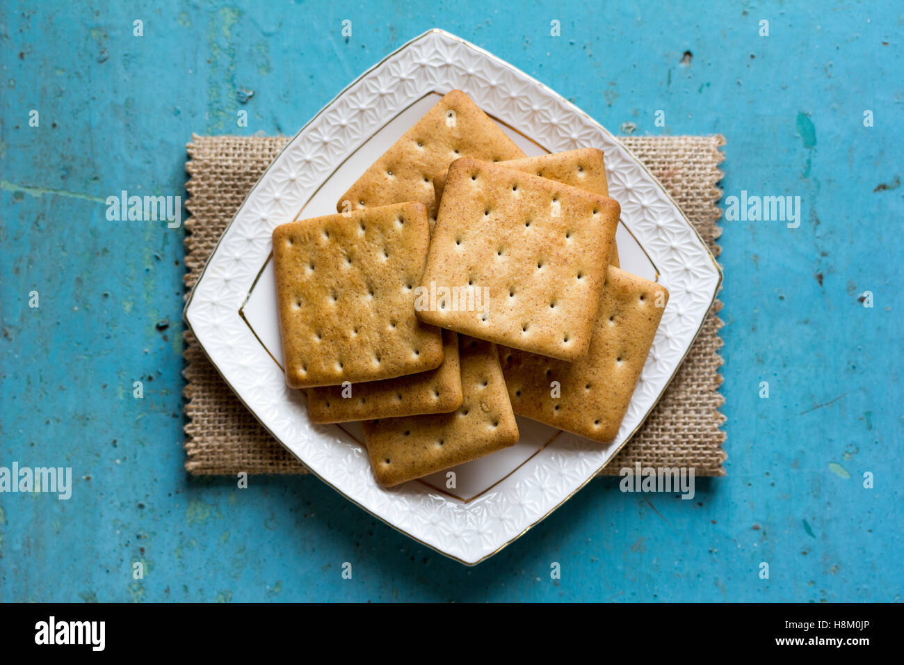 Cracker biscuits in a white ceramic square saucer on linen napkin on old blue background close-up. Top view Stock Photo