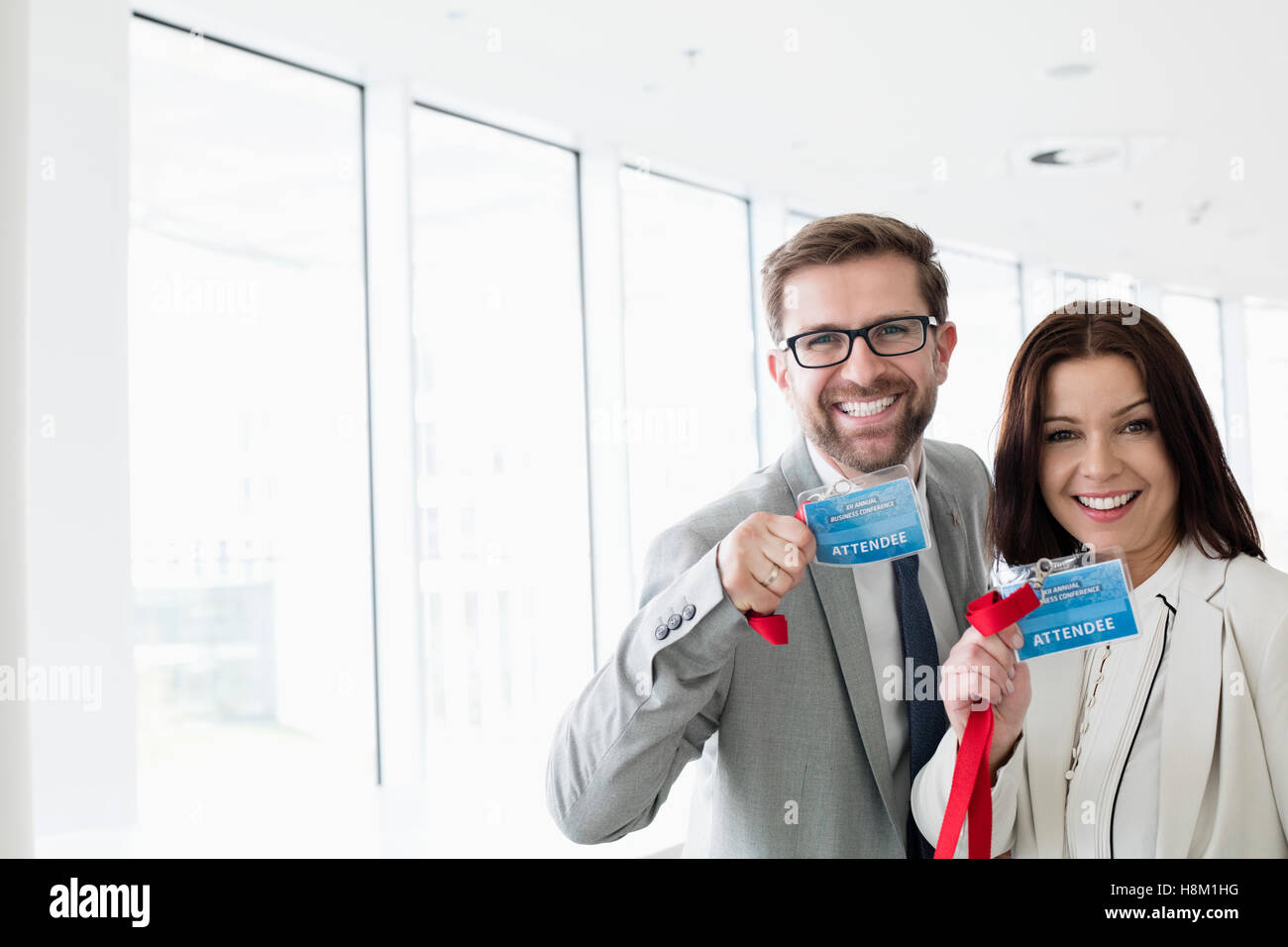 Portrait of happy business people showing identity cards in convention center - Stock Image