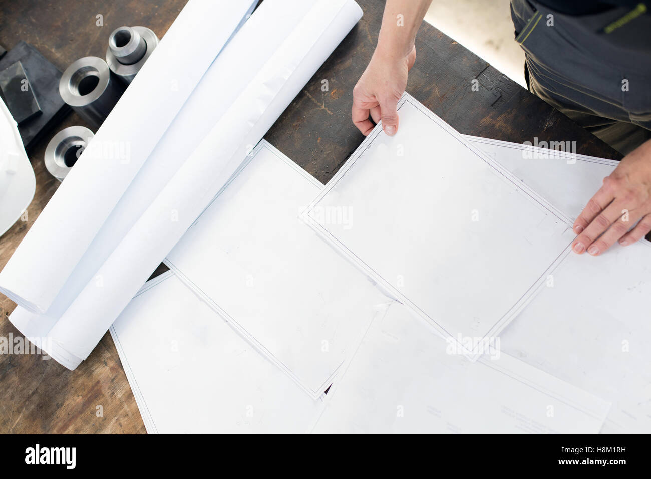 High angle view of mid adult architect with blueprints at table in industry - Stock Image