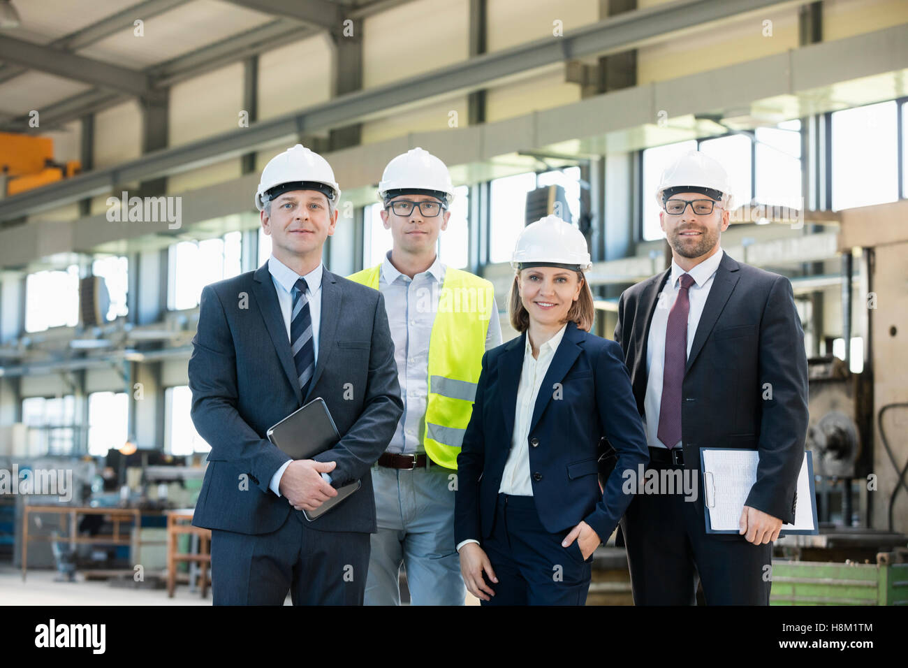 Portrait of confident business people wearing hardhats in metal industry - Stock Image