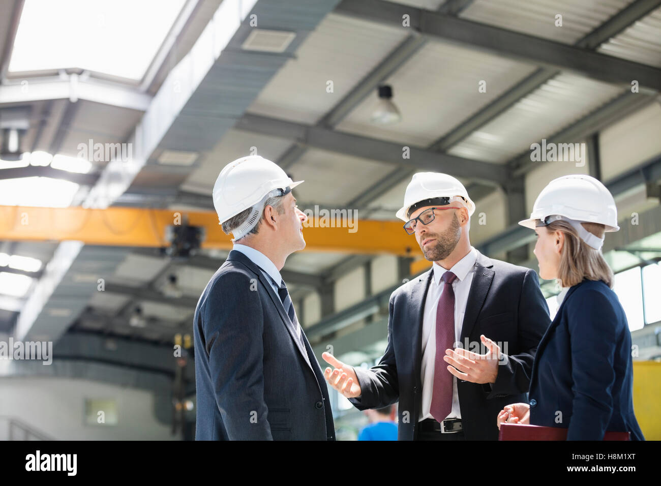 Business people wearing hardhats having discussion in metal industry - Stock Image