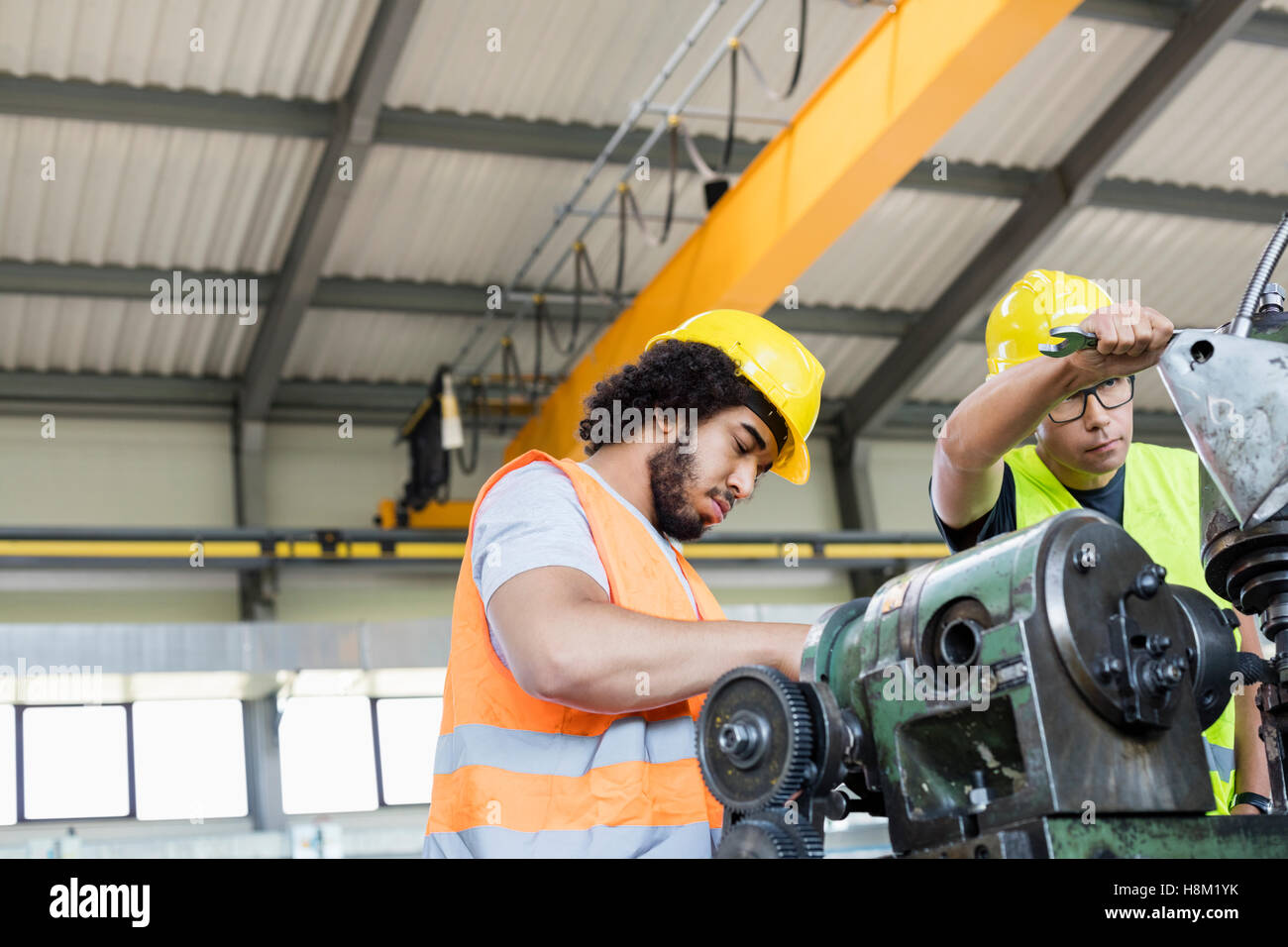 Low angle view of manual workers working on machinery in metal industry Stock Photo