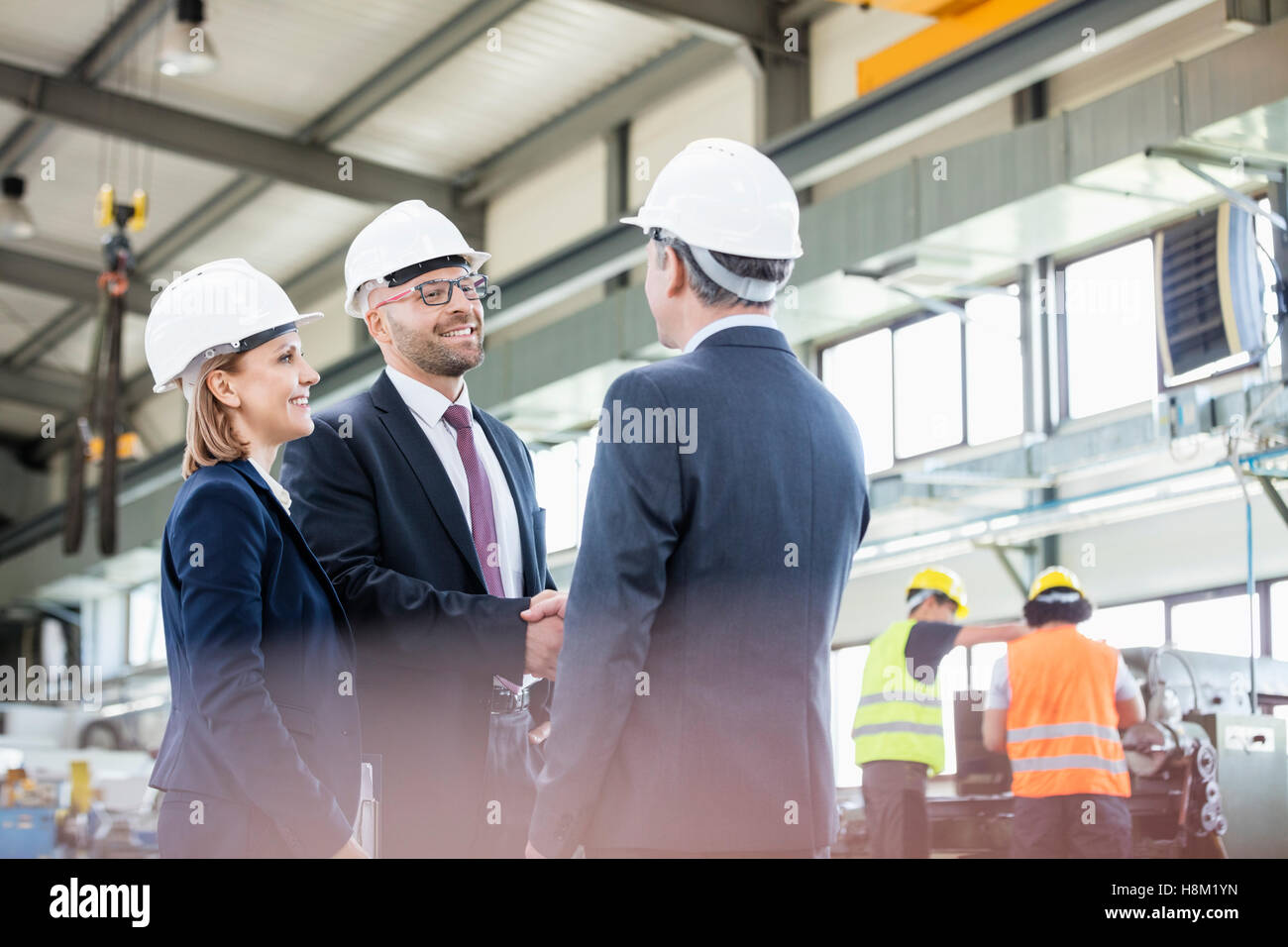 Businessmen shaking hands with workers working in background at metal industry Stock Photo