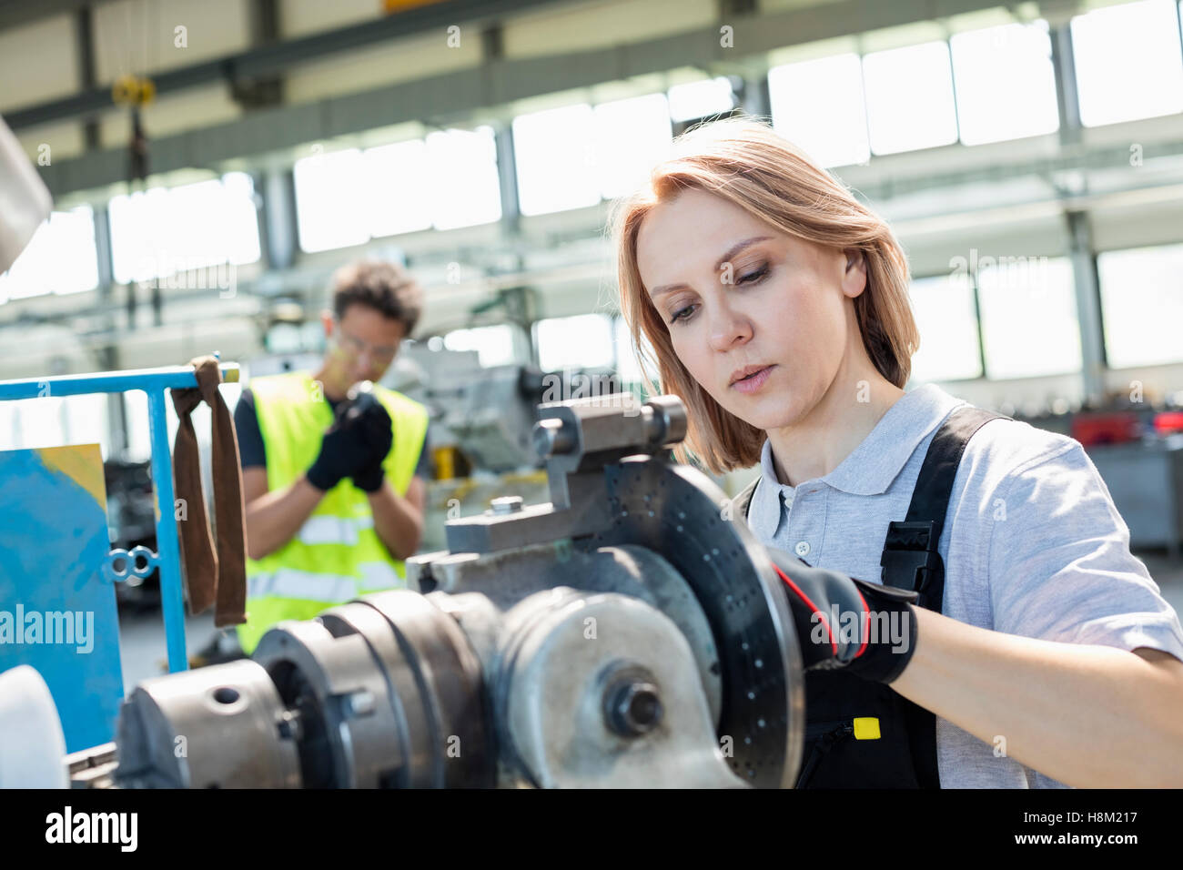 Mature female worker working on machinery with colleague in background at industry Stock Photo