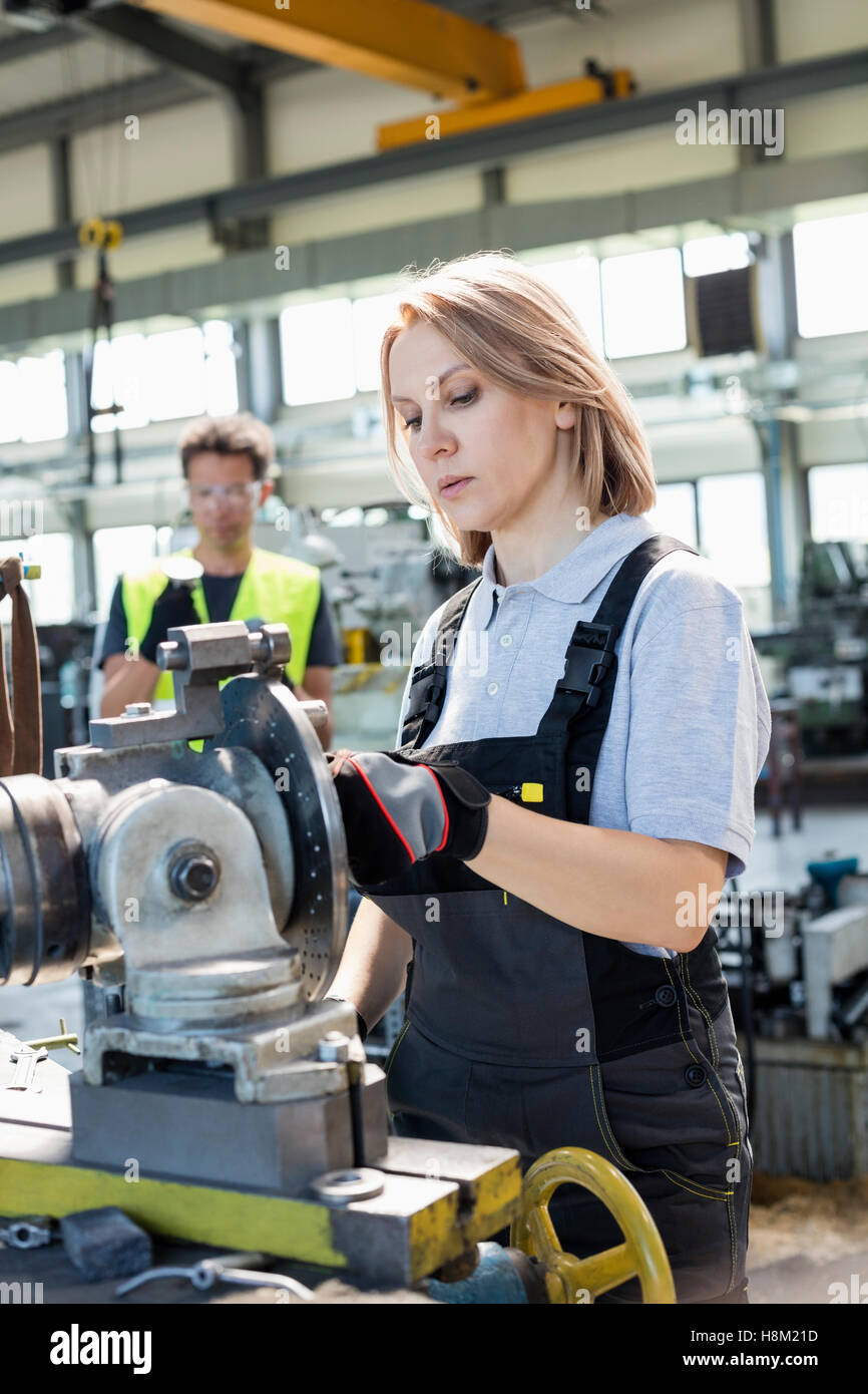 Mature female worker working on machinery with colleague in background at factory Stock Photo