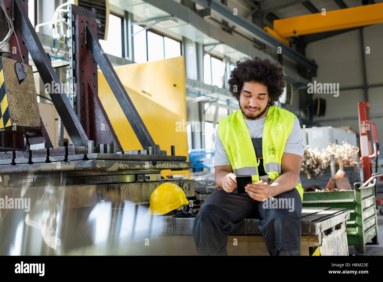 Young manual worker using mobile phone in metal industry Stock Photo