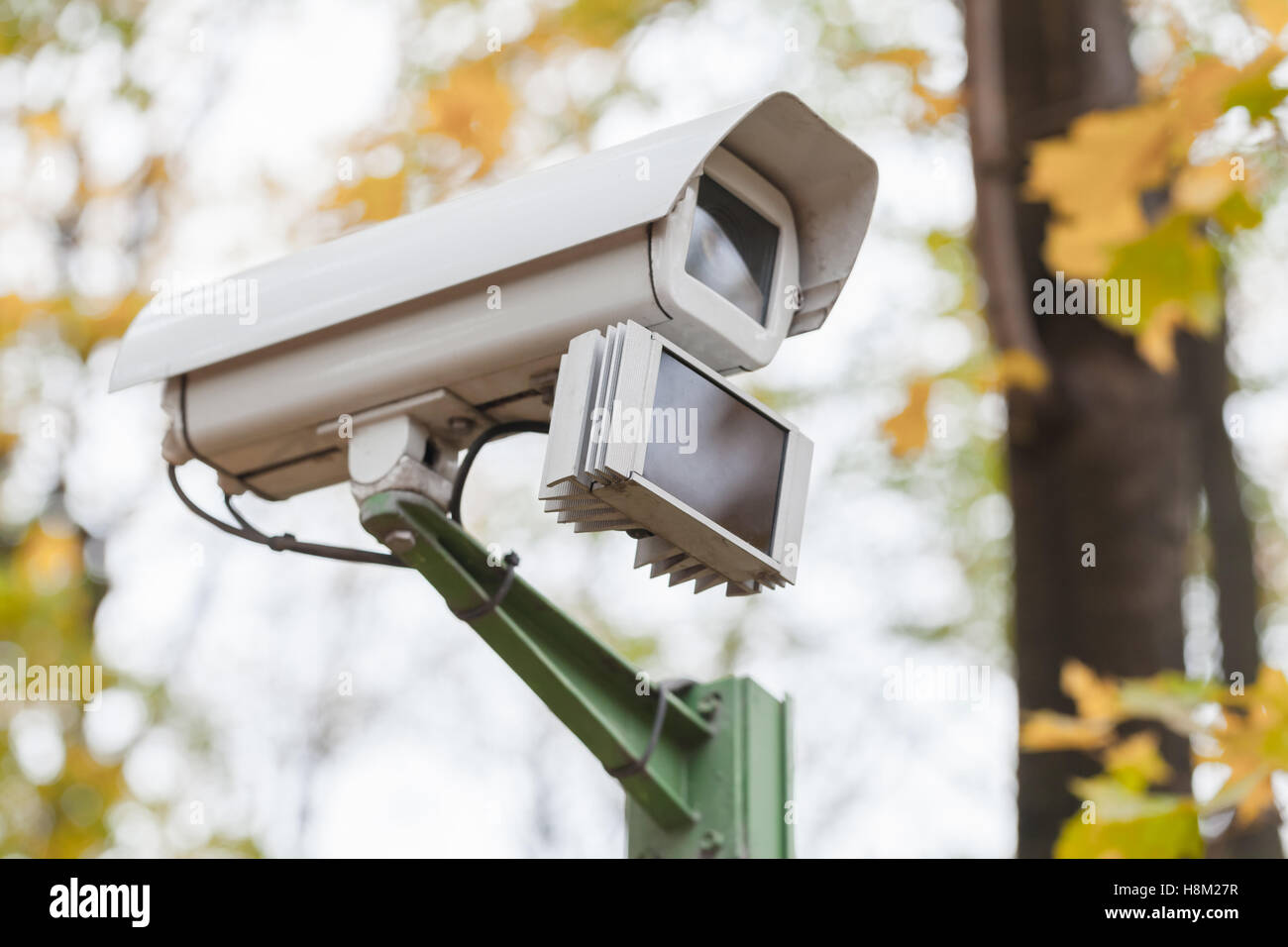 Close-up photo of an outdoor surveillance camera with motion detector in autumnal park - Stock Image