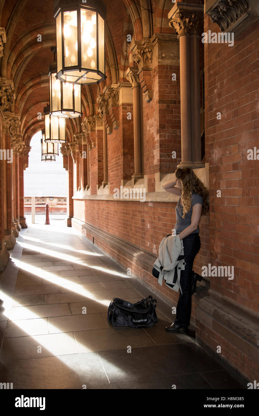 Lady waiting in alleyway near St Pancras station with bag Stock Photo