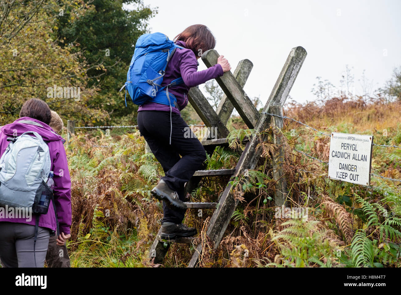 Bilingual 'Danger keep out' sign on a public footpath with hikers climbing a ladder stile over a barbed - Stock Image