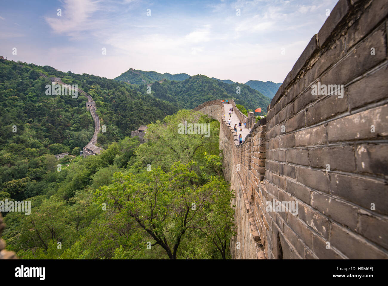 Mutianyu, China - Landscape view of tourists taking pictures and walking on the Great Wall of China. The wall stretches - Stock Image