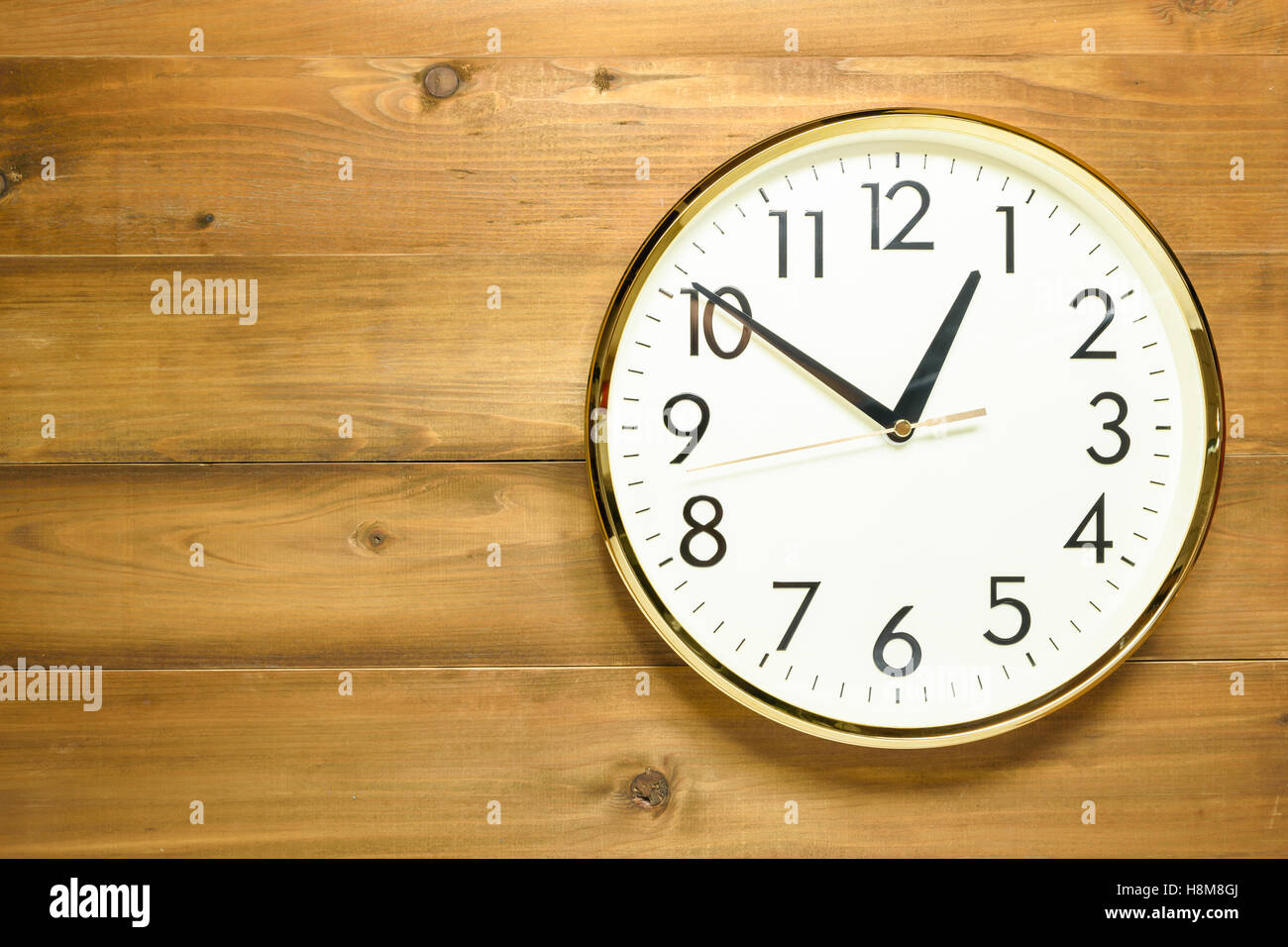 wall clock on the wooden wall early afternoon - Stock Image