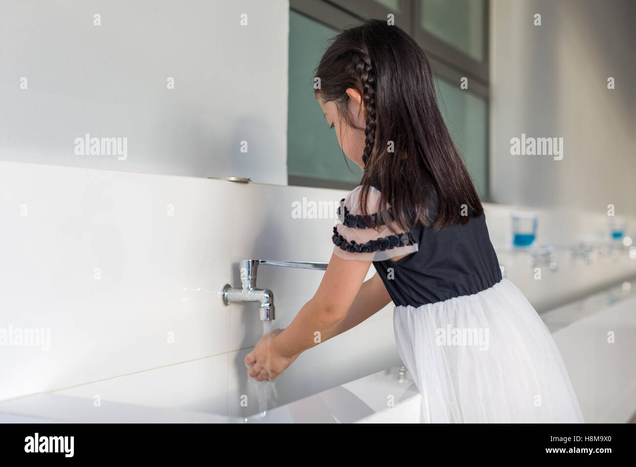 Child washing hands from water tap at school. - Stock Image