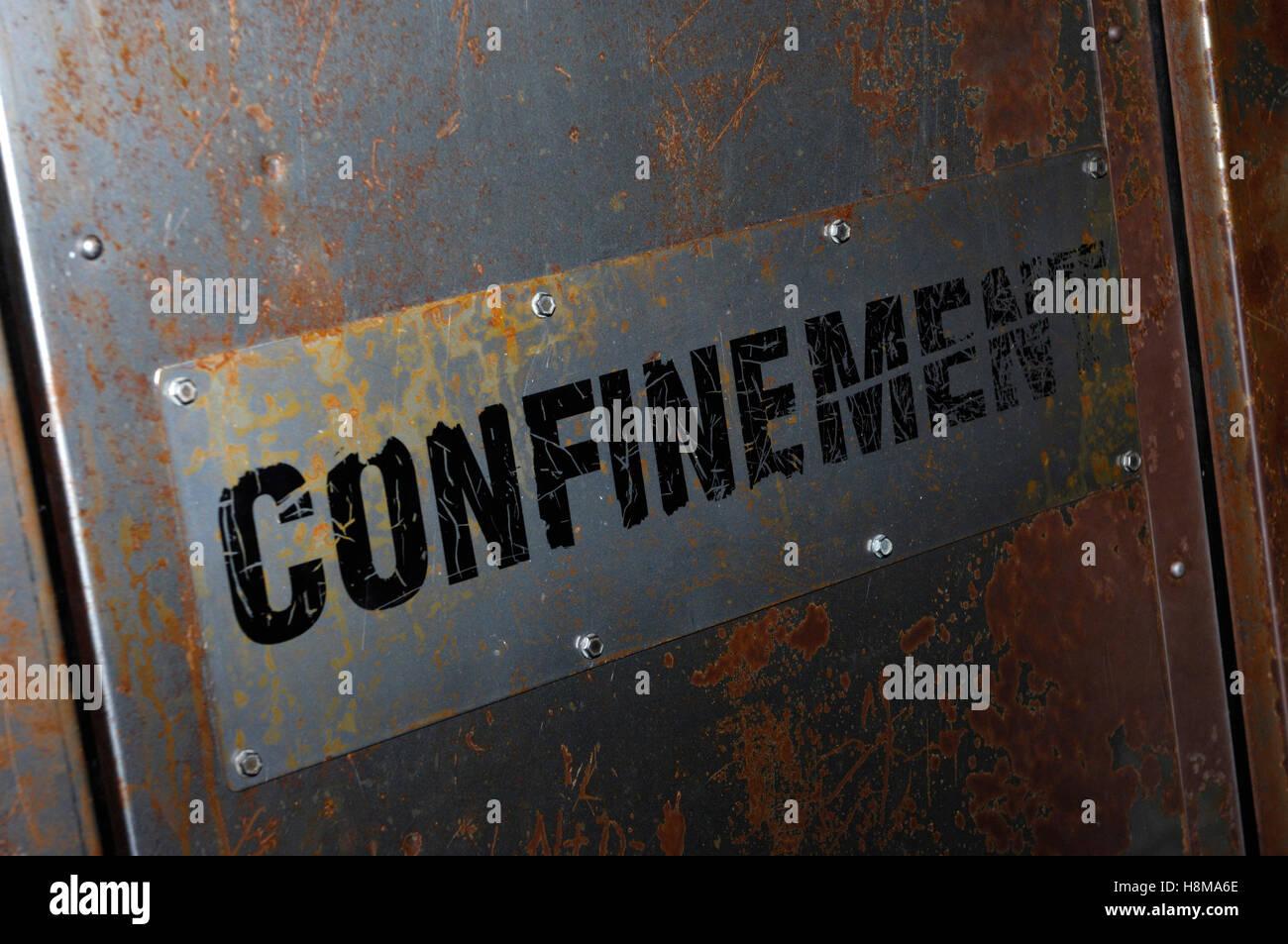 Confinement sign on a rusty metal door - Stock Image