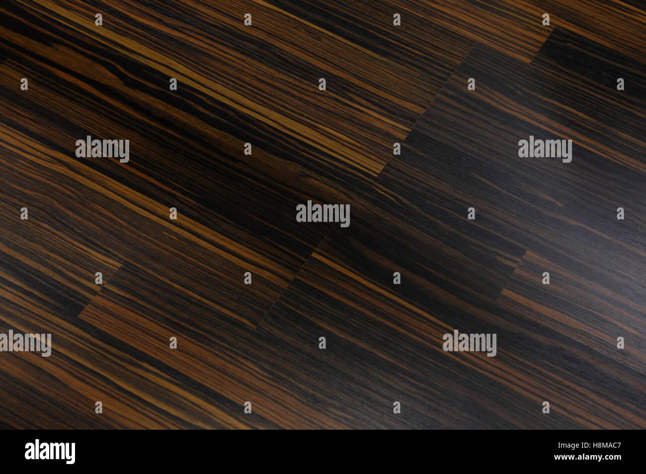 Dark brown wood laminated floor, background - Stock Image