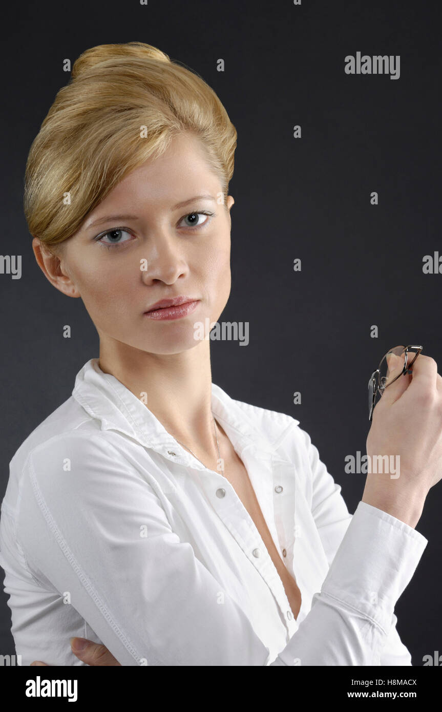 Portrait of a young businesswoman holding eyeglasses in her hand - Stock Image