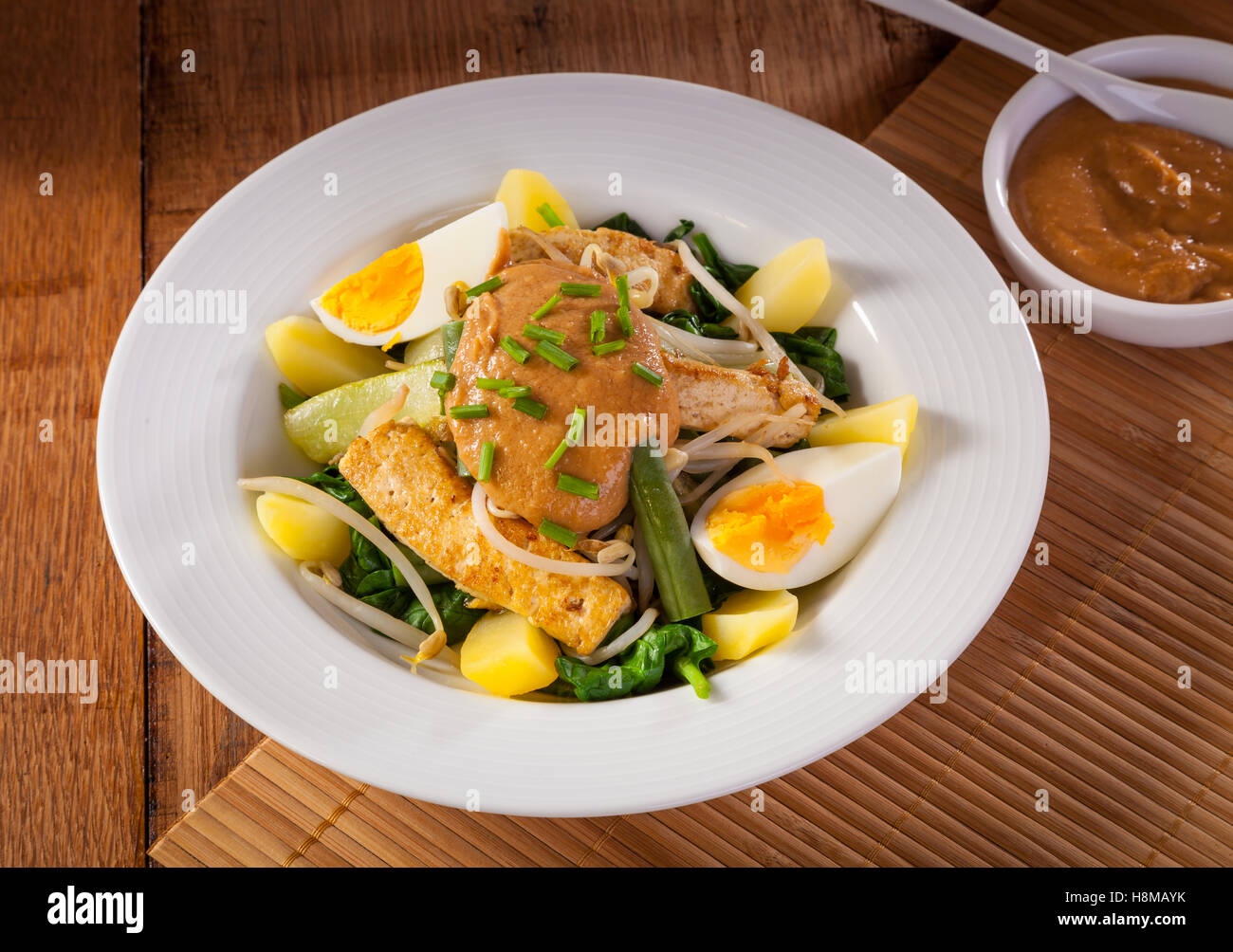 Gado-gado Indonesian salad served with peanut sauce. Ingredients: tofu, spinach, string beans, soy sprouts, potatoes, - Stock Image