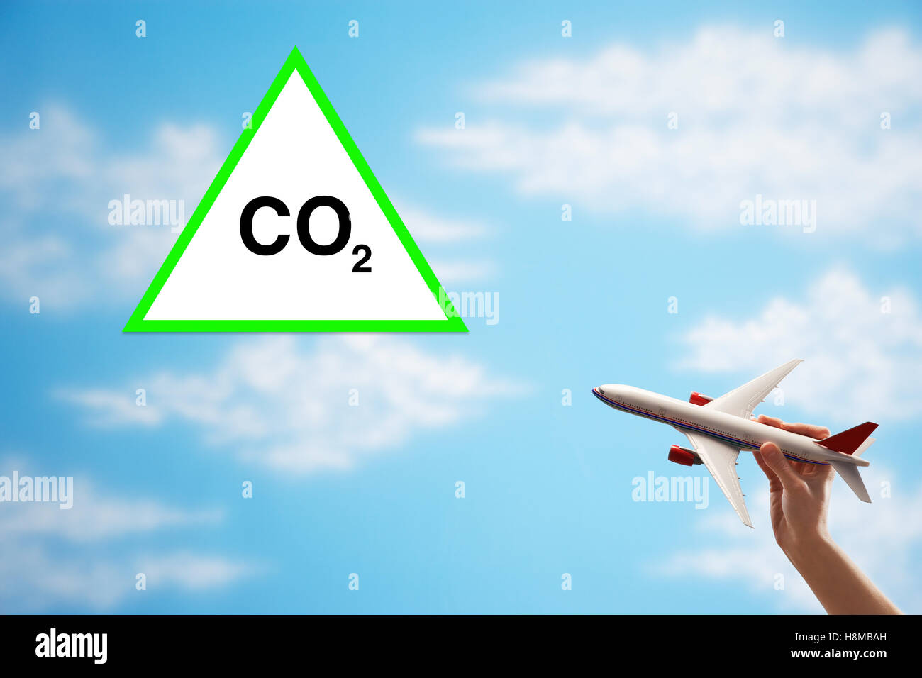 Closeup of woman's hand flying toy plane against cloudy sky with warning CO2 sign - Stock Image
