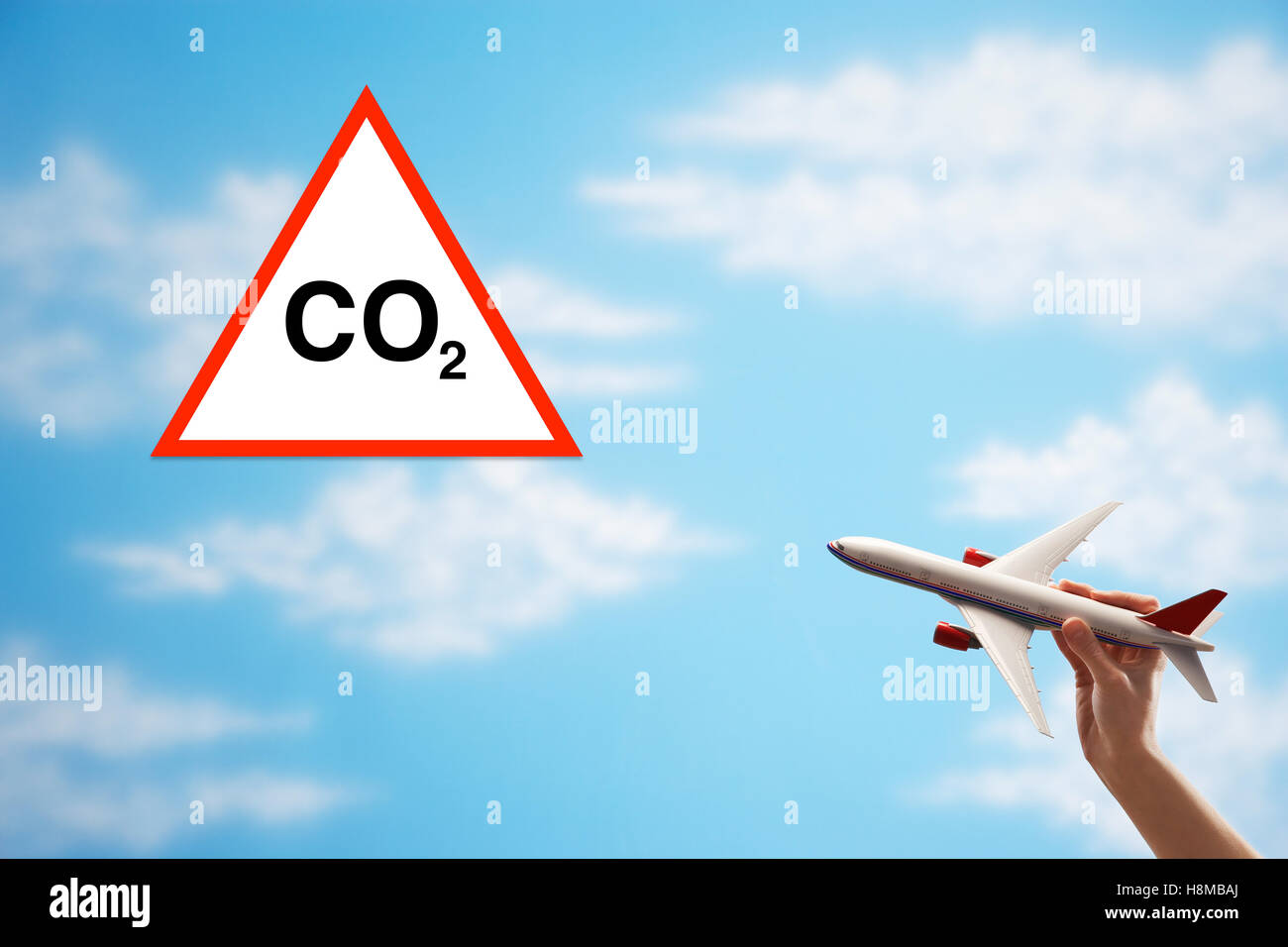 Closeup of woman's hand flying toy plane against cloudy sky with warning CO2 sign Stock Photo