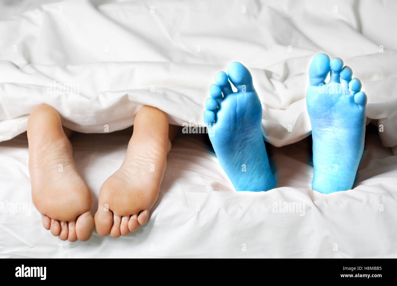 Closeup of a couple lying in bed barefeet - Stock Image